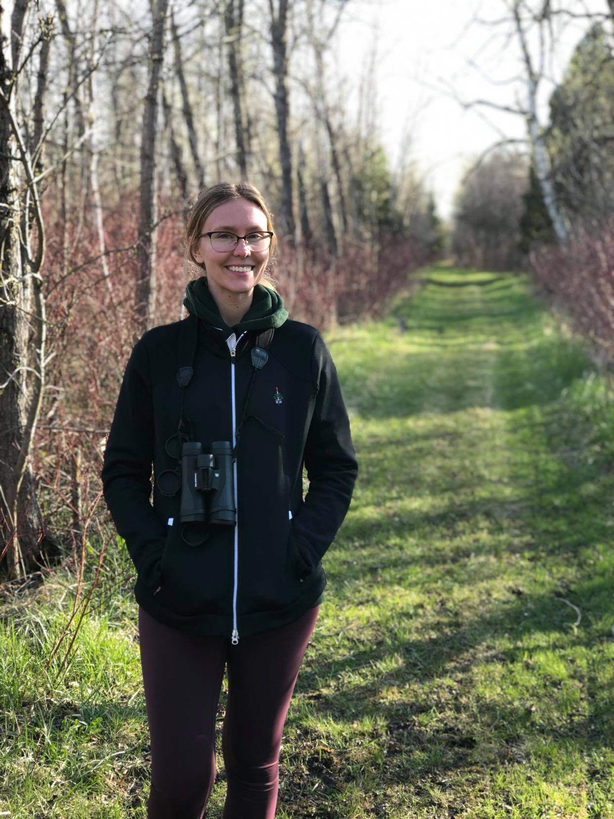Gabby Nichols wearing binoculars and smiling in front of grassy path lined by tree silhouettes.