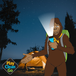 Steward bigfoot with flashlight beaming from under face. Orange tent and starry sky in background.